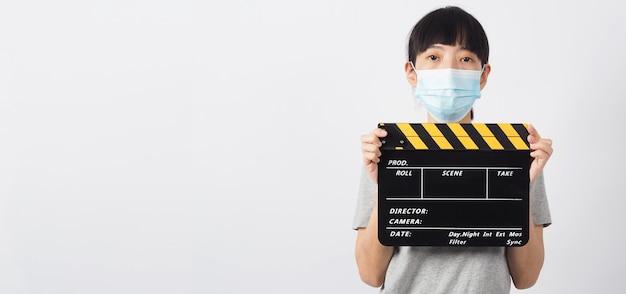 Mulher asiática usar máscara facial e mão segurando claquete ou ripa preta sobre fundo branco.