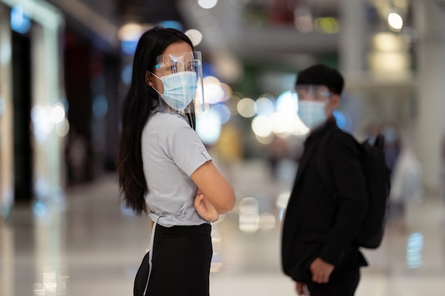 Mulher asiática usar uma máscara de proteção contra vírus. no shopping