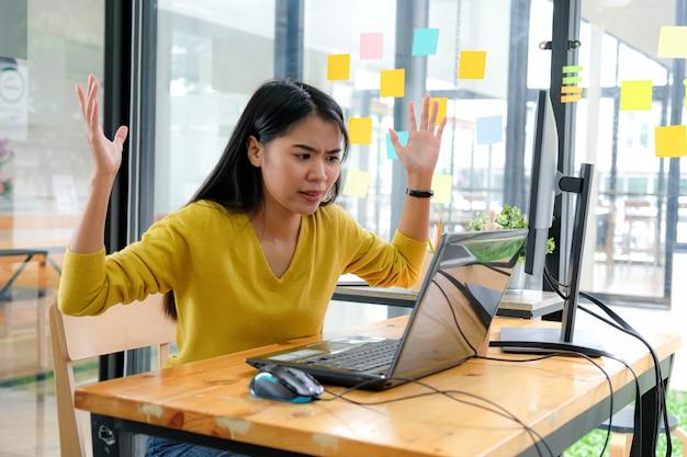 Mulher asiática veste uma camisa amarela, olha para a tela do laptop e mostra uma maneira séria.