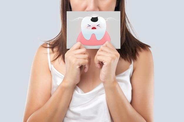 Mulher asiática vestida de branco segurando um papel branco, a imagem de desenho animado de cárie de sua boca contra o fundo cinza, dente cariado, o conceito com gengivas e dentes de saúde