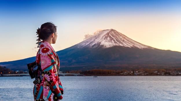 Mulher asiática vestindo quimono tradicional japonês na montanha fuji. pôr do sol no lago kawaguchiko, no japão.