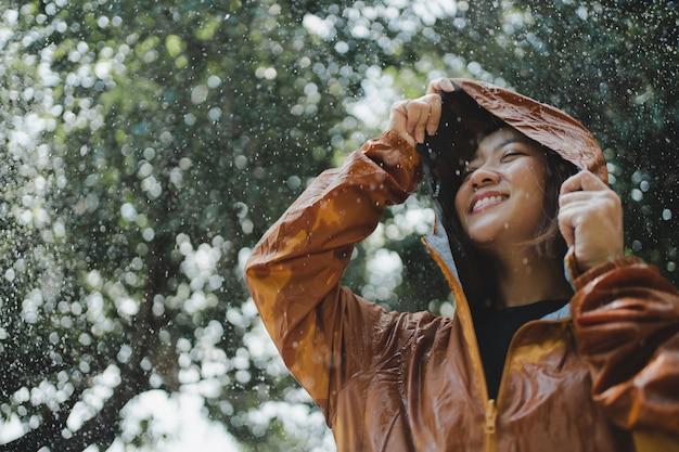 Mulher asiática vestindo uma capa de chuva ao ar livre. ela está feliz.