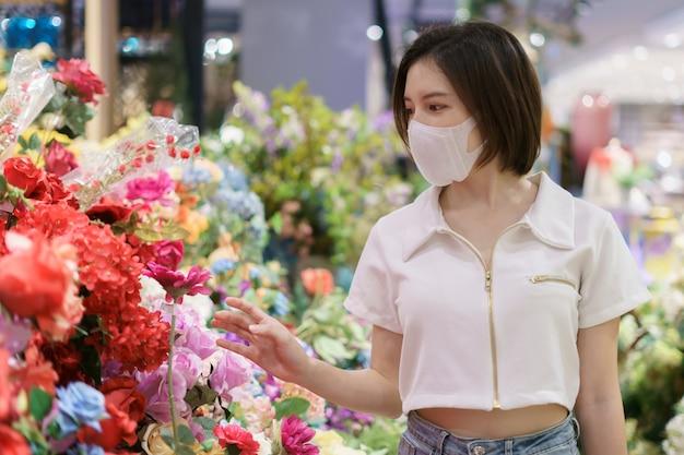 Mulher asiática, vestindo uma máscara facial em uma loja de flores