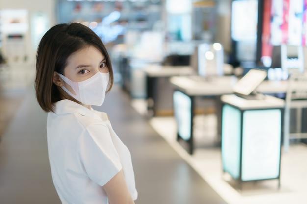 Mulher asiática, vestindo uma máscara facial no shopping