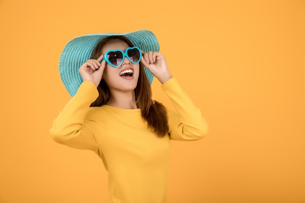 Mulher asiática vestir conceito férias com uma camisa amarela óculos de sol e chapéus são azuis e fazem rostos muito felizes.