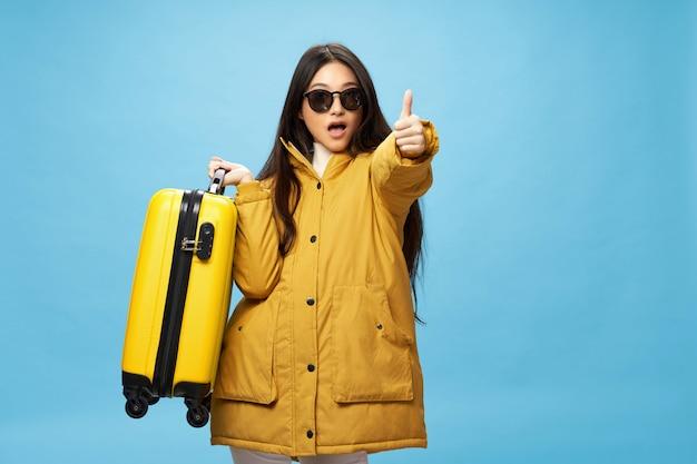 Mulher asiática viaja com uma mala nas mãos, férias, estúdio