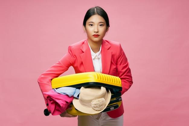 Mulher asiática viaja com uma mala nas mãos, férias.