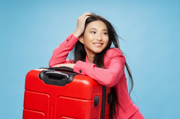 Mulher asiática viaja com uma mala nas mãos, férias