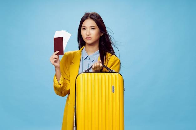 Mulher asiática viaja com uma mala nas mãos