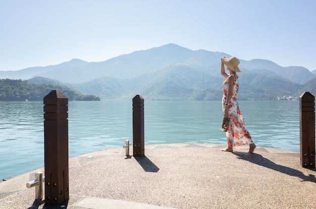 Mulher asiática viajando com chapéu andando em uma doca no lago sun moon, taiwan
