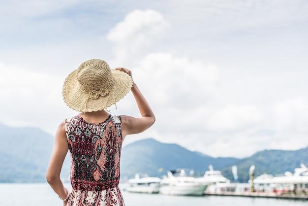 Mulher asiática viajando com chapéu em pé no lago sun moon, taiwan