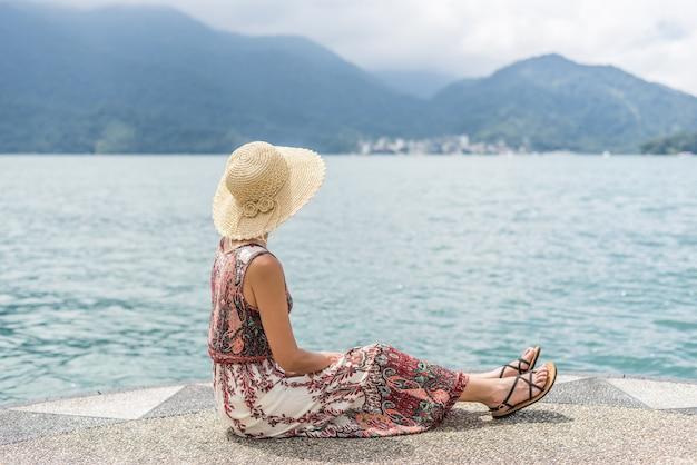 Mulher asiática viajando com chapéu sentada em um píer no lago sun moon, taiwan