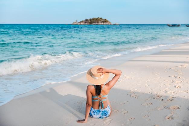 Mulher asiática viajante com biquíni e chapéu relaxando na praia do mar durante o dia em koh lipe, satun, tailândia