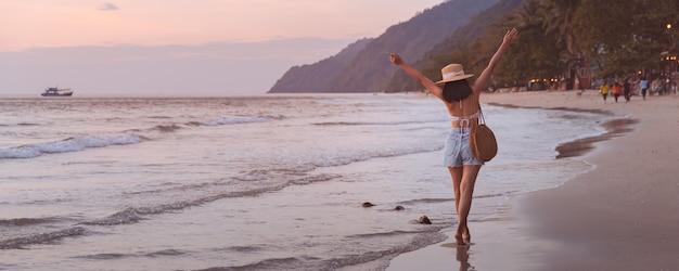 Mulher asiática viajante com chapéu relaxando e passeando na praia ao pôr do sol em koh chang, trat, tailândia