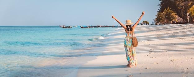Mulher asiática viajante feliz com vestido relaxante e passear na praia à noite em koh lipe, satun, tailândia,