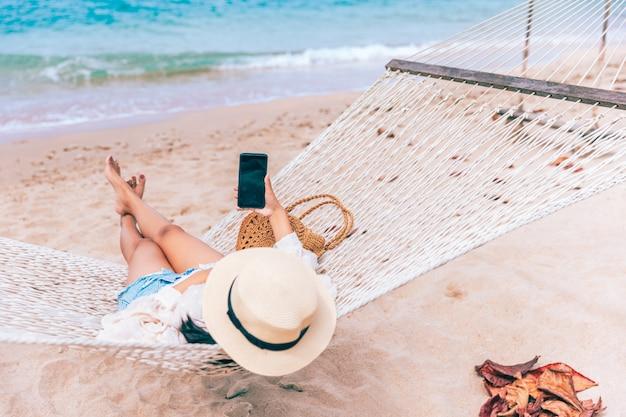 Mulher asiática viajante feliz usando telefone celular e relaxando em uma rede na praia em koh chang, trad, tailândia