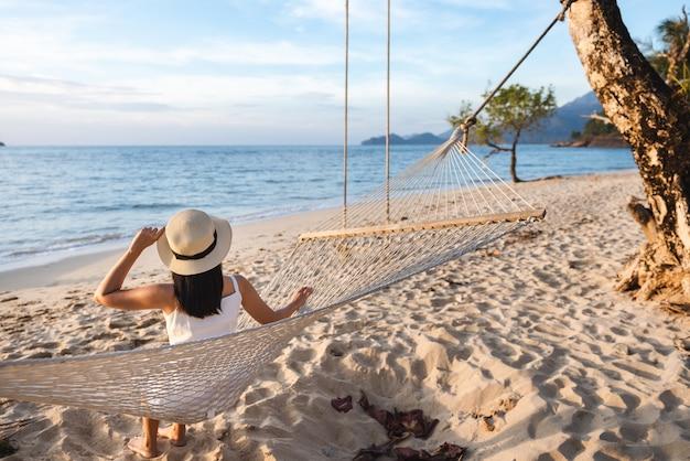 Mulher asiática viajante relaxando em uma rede na praia em koh chang trad tailândia