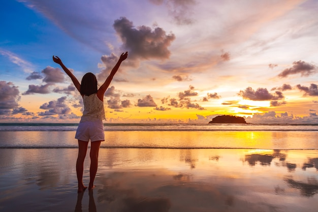 Mulher asiática viajante relaxando na praia de kata ao pôr do sol em phuket, tailândia