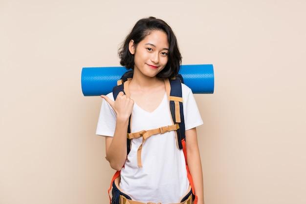 Mulher asiática viajante sobre isolado apontando para o lado para apresentar um produto