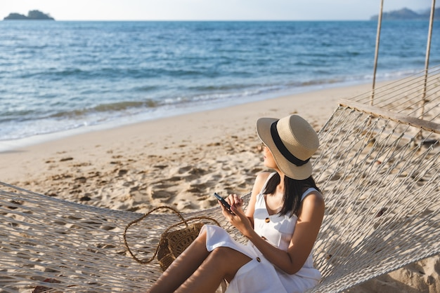 Mulher asiática viajante usando telefone celular e relaxando em uma rede na praia em koh chang trad tailândia