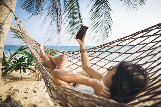 Mulher asiática viajante usando telefone celular e relaxando em uma rede na praia em koh mak, tailândia