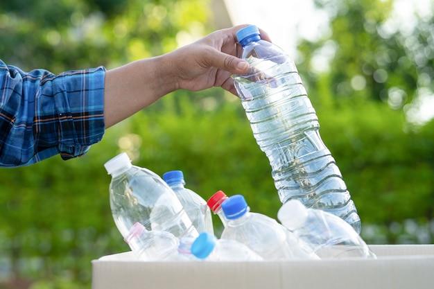 Mulher asiática voluntária carrega garrafas plásticas de água para a lixeira do parque