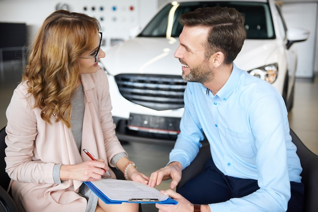 Mulher assinando contrato com seu parceiro