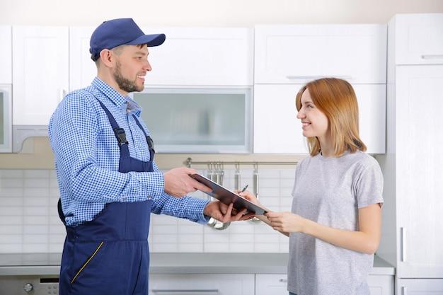 Mulher assinando recibo de serviço de encanador em casa