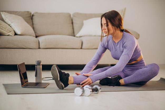 Mulher assistindo a tutoriais e treinando em casa no tapete usando corda de pular e halteres
