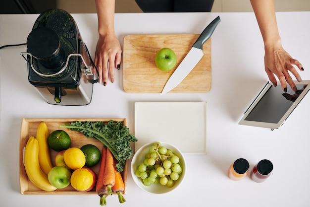 Mulher assistindo a um vídeo de blogueiro de culinária no computador tablet ao fazer um smoothie saboroso e saudável com couve, frutas e vegetais, vista de cima