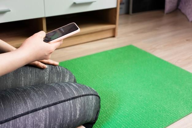 Mulher assistindo aulas de treinamento de pilates em smartphone, sentado na esteira verde de exercícios em casa.
