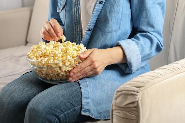 Mulher assistindo filme no sofá e come pipoca. comida para assistir filmes
