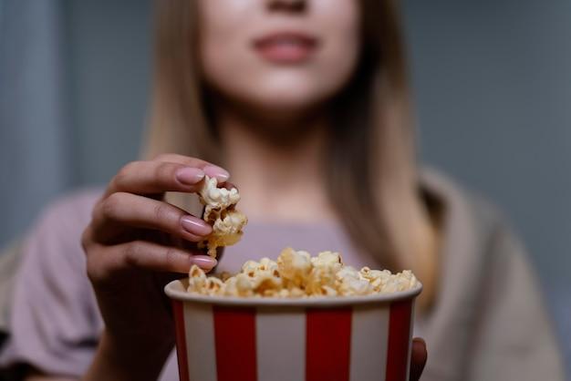 Mulher assistindo tv e comendo pipoca de perto