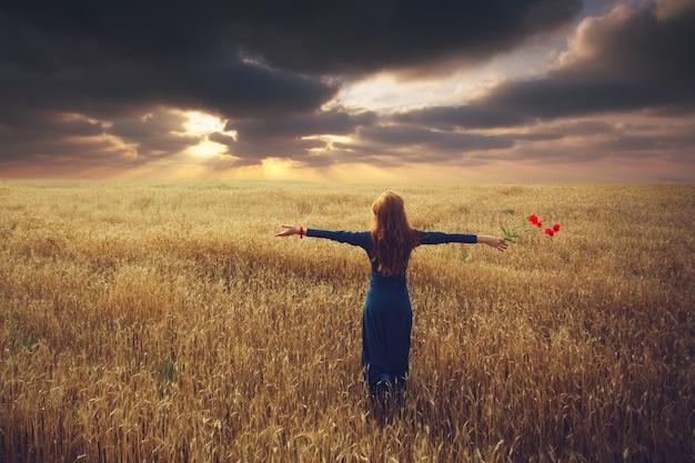 Mulher assistir o pôr do sol em um campo com os braços estendidos