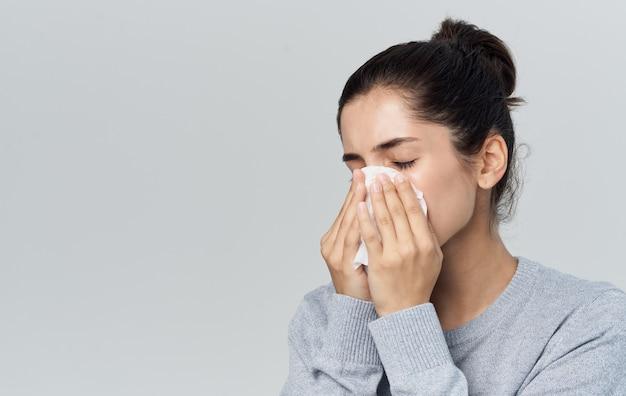 Mulher assoa o nariz em um fundo cinza de problemas de saúde nariz escorrendo do guardanapo. foto de alta qualidade