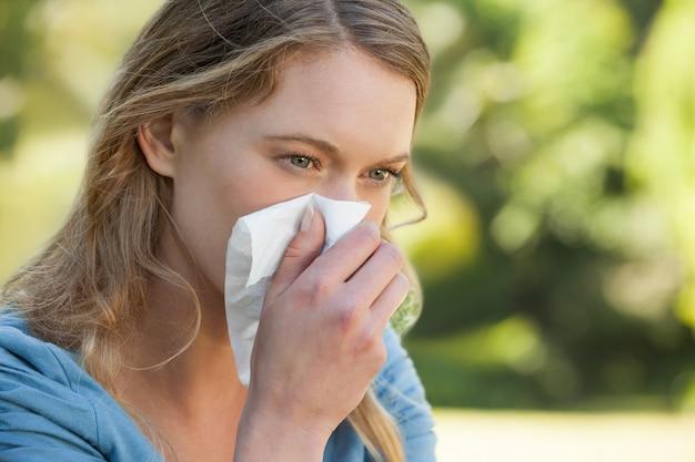 Mulher assoar o nariz com lenço de papel no parque