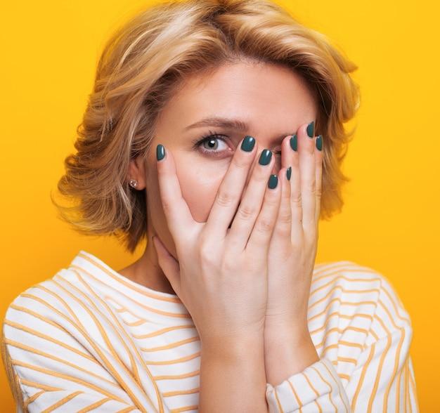 Mulher assustada cobrindo o rosto com as palmas das mãos, olhando para a câmera e posando na parede amarela de um estúdio