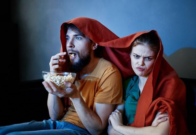 Mulher assustada com uma manta vermelha na cabeça e um homem com um prato de pipoca