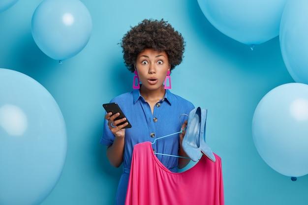Mulher assustada e emotiva em roupas elegantes, escolhe vestido e sapatos de salto alto para se vestir na festa de aniversário, segura smartphone