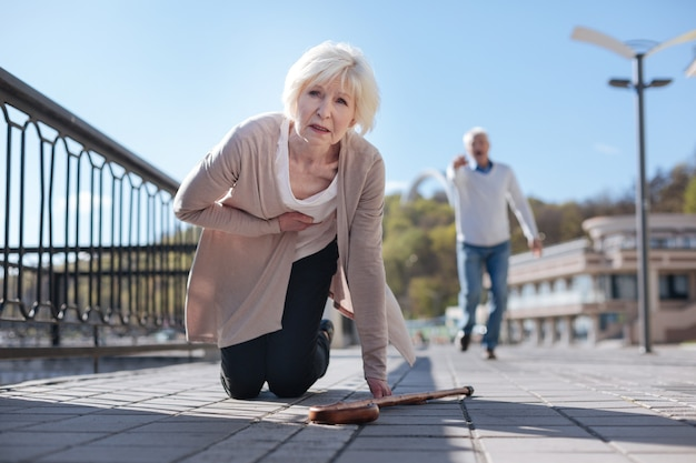 Mulher assustada e intrigada descansando e sentindo um ataque cardíaco enquanto um homem idoso corria para ajudá-la