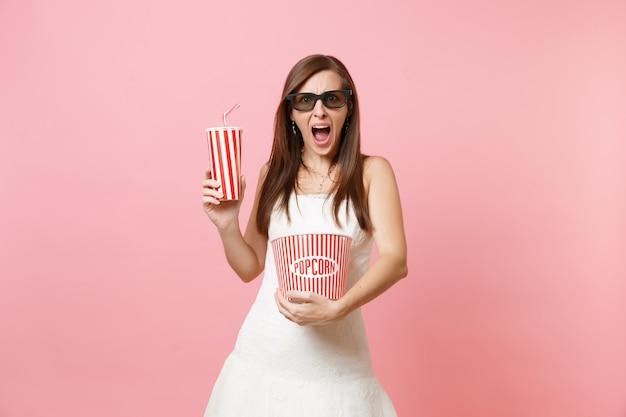 Mulher assustada em óculos 3d de vestido branco gritando assistindo filme de cinema segurando um balde de pipoca em um copo plástico de refrigerante ou cola