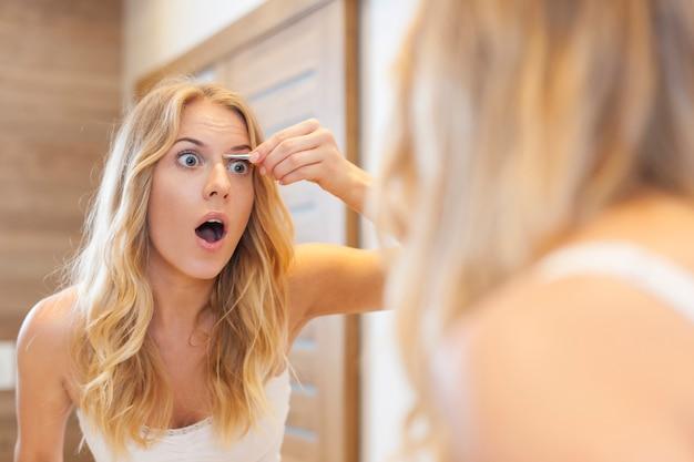 Mulher assustada pinçando as sobrancelhas no banheiro