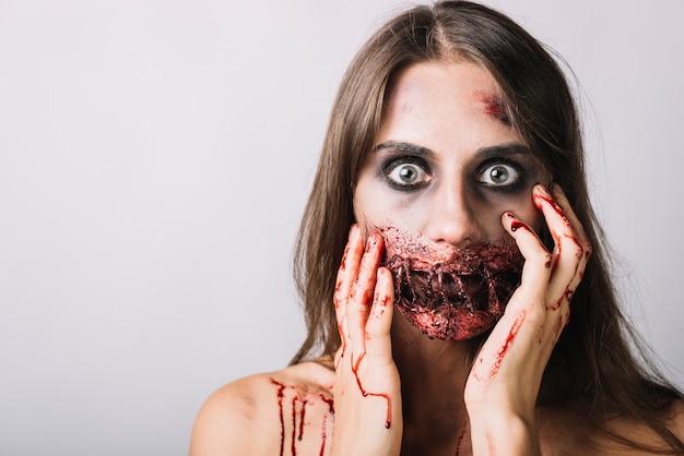 Mulher assustada, tocando o rosto danificado com as mãos ensanguentadas