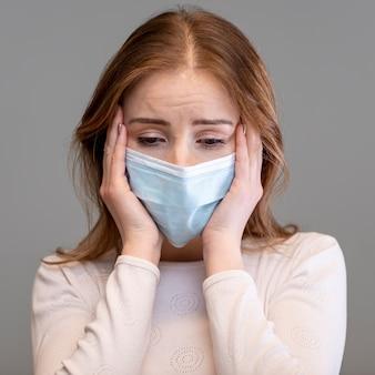 Mulher assustada usando máscara cirúrgica