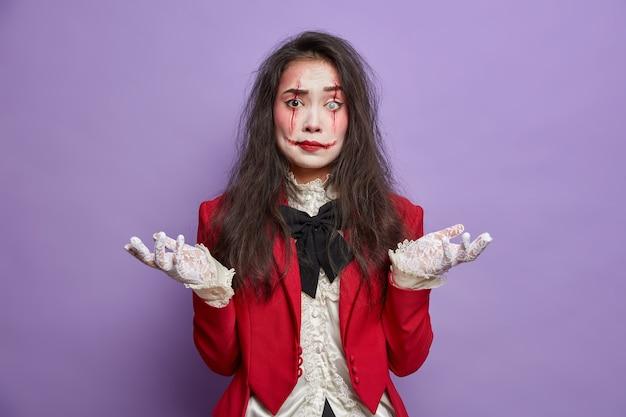 Mulher assustadora e hesitante tem imagens de poses de zumbi com caveiras de açúcar e cicatrizes de sangue se preparando para o festival de halloween isolado na parede roxa