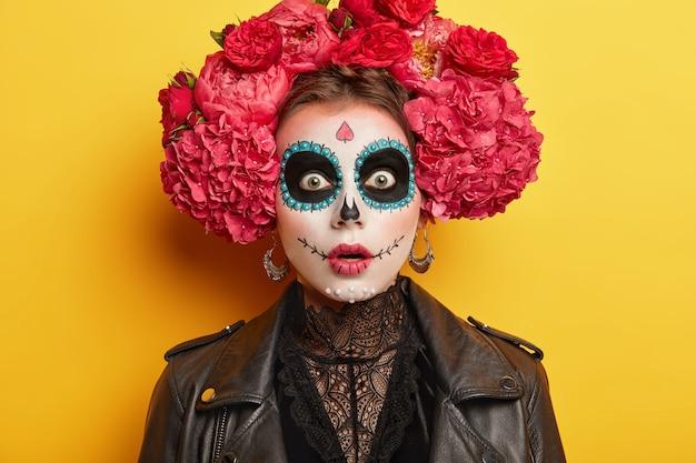 Mulher assustadora usa maquiagem de halloween de terror, tem expressão assustada, persegue círculos pintados de preto ao redor dos olhos, usa grinalda de flor vermelha grande, isolada sobre fundo amarelo.