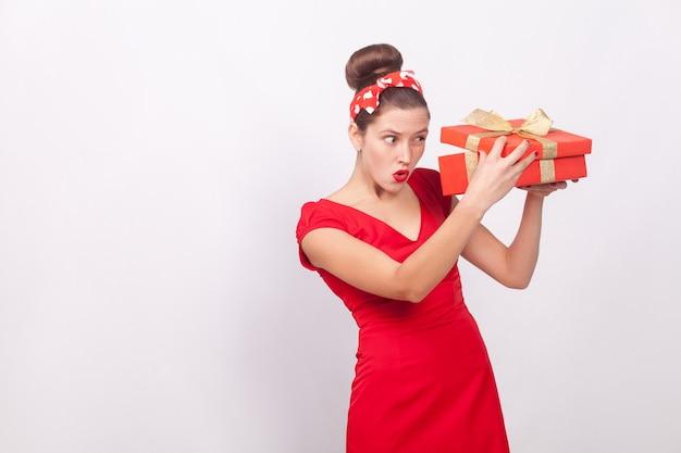 Mulher astuta olhando para dentro da caixa de presente