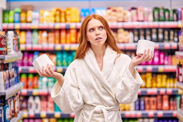 Mulher atenciosa está escolhendo o melhor papel higiênico da loja, vestindo roupão branco, estande se divertindo no departamento de utensílios domésticos do supermercado