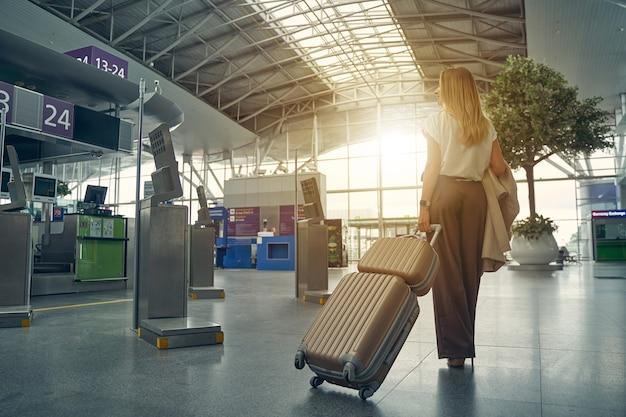 Mulher atenta carregando sua bagagem e se dirigindo ao portão necessário para levá-la sentar no avião