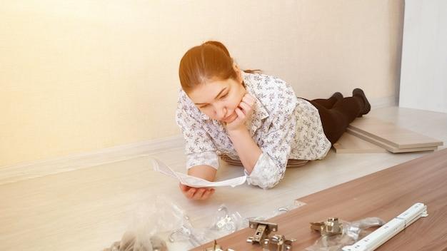 Mulher atenta com rabo de cavalo deitada no chão de ladrilho e analisa a nota de orientação para a montagem do armário da cozinha vista de perto